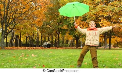 smiling boy with umbrella have fun in autumn park