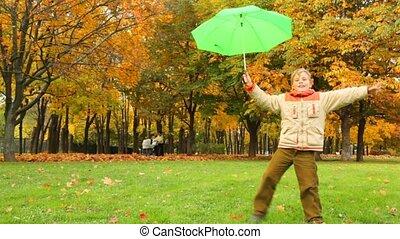 smiling boy with umbrella have fun in autumn park