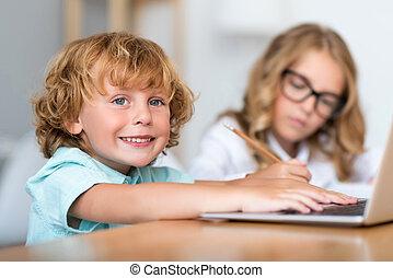 Smiling boy working on laptop