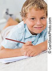 Smiling boy writing lying on the floor