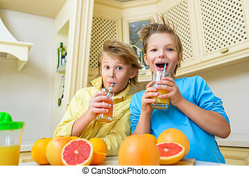 Smiling boys enjoying with glass of yellow juice at kitchen