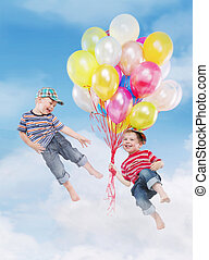 Smiling boys flying with balloons