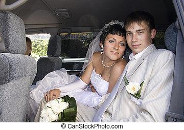 Smiling bride and groom in wedding car