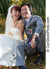smiling bride and groom sitting in park (2)