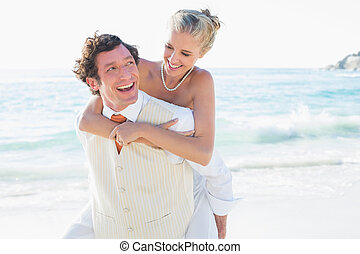 Smiling bride getting a piggy back from new husband at the...