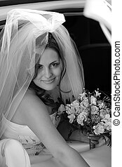Smiling bride getting out of wedding car limousine