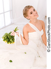 Smiling bride holding flowers
