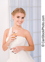 Smiling bride holding glass with champagne