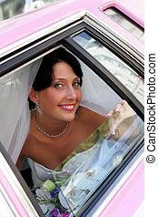 Smiling bride in pink wedding car limo