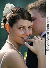 Smiling Bride looking over husbands shoulder