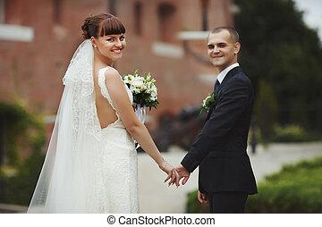 Smiling bride looks over her shoulder holding groom's hand