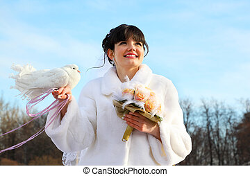 smiling bride with bouquet holds white dove and looks into...