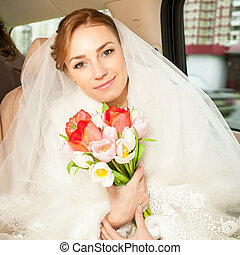 Smiling bride with bouquet on backseat of car