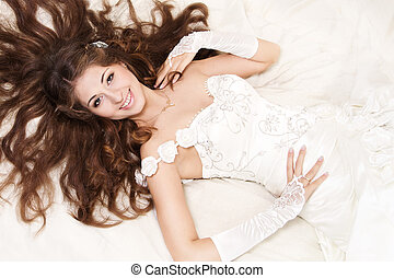 Smiling bride with curly long hair lying over white. High...