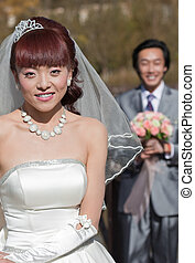 smiling bride with groom in background (2)