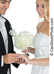 Smiling bridegroom putting the wedding ring on his wife's finger on white background