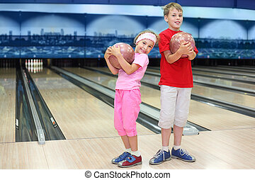 Smiling brother and sister hold balls in bowling club; bowling alleys and skittles