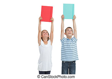 Smiling brother and sister holding their notebooks above their head while posing on white background