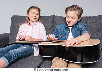 smiling brother and sister playing on guitar together while sitting on sofa