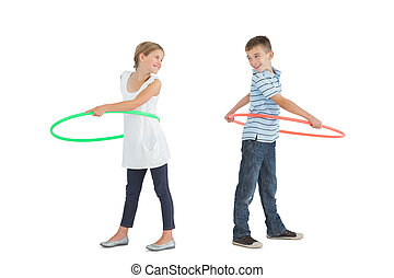 Smiling brother and sister playing with hula hoop together...