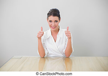 Smiling brown haired businesswoman giving thumbs up to camera