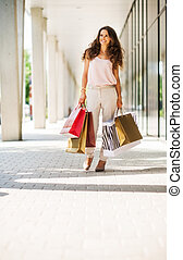 Smiling, brown-haired woman walking with colourful shopping bags