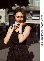 Smiling brunette girl with bronze tan posing on the street in a fashionable dress