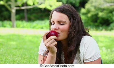 Smiling brunette haired woman eating a red apple in a park