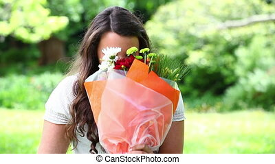 Smiling brunette holding a bunch of flowers