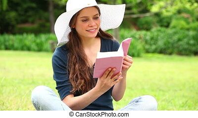 Smiling brunette holding a novel in the countryside