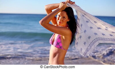 Smiling brunette holding a sarong on the beach