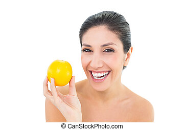 Smiling brunette holding an orange and looking at camera