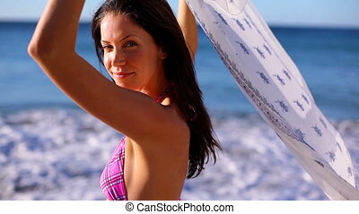 Smiling brunette holding her sarong on the beach