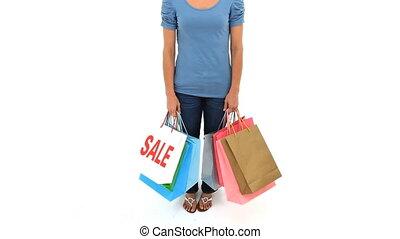 Smiling brunette holding shopping bags