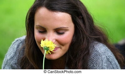 Smiling brunette holding while smelling a flower