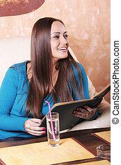 Smiling brunette in blue at cafe table