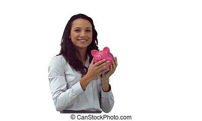 Smiling brunette in slow motion holding a piggy bank