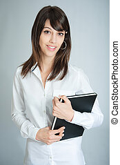 Smiling brunette in white shirt carrying a book