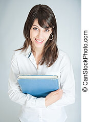 Smiling brunette in white shirt holding a book
