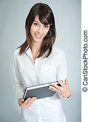 Smiling brunette in white shirt with black book