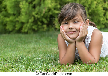 Smiling brunette little girl lying on the grass