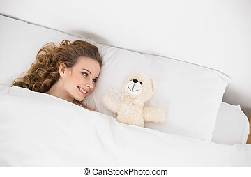 Smiling brunette lying next to teddy bear