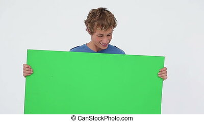 Smiling brunette man holding a blank poster against a white...