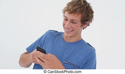 Smiling brunette man texting on his cellphone
