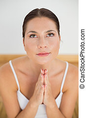 Smiling brunette meditating with hands together