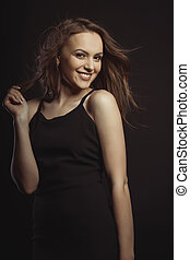 Smiling brunette model in black dress with curly hair in motion