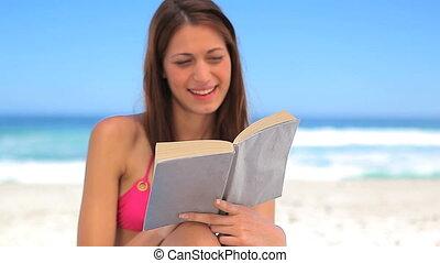 Smiling brunette reading an interesting novel on the beach