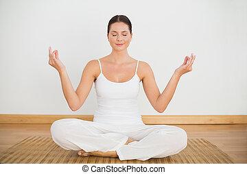 Smiling brunette sitting in lotus pose looking at camera