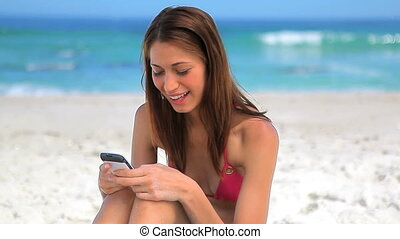 Smiling brunette sitting on the sand while sending a text