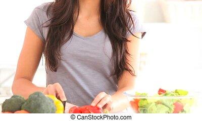 Smiling brunette slicing pepper
